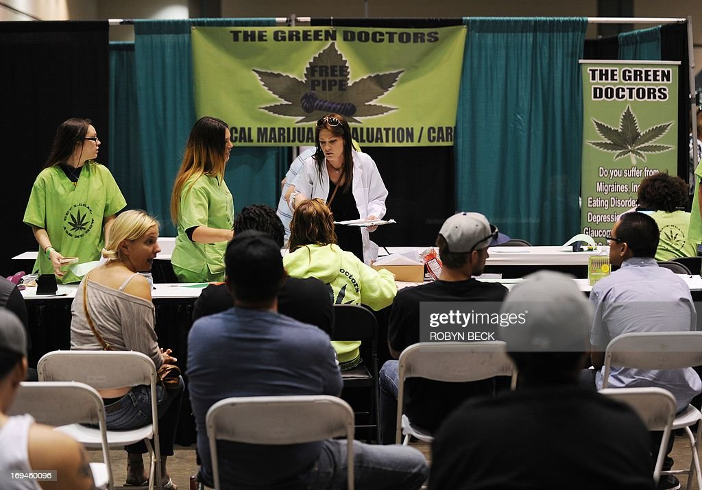 People wait to be screened for medical marijuana identification cards at the Green Doctors display, at the HempCon medical marijuana show, May 24, 2013 at the Los Angeles Convention Center. Thousands of marijuana enthusiasts gathered for the three-day event for exhibits of medical marijuana dispensaries, collectives, evaluation services, legal services and equipment and accessories. Under California state law, people suffering from chronic diseases have the right to grow, buy and use marijuana for medical purposes when recommended by a doctor. In 2003 the Medical Marijuana Protection Act, established an identification card system for medical marijuana patients.