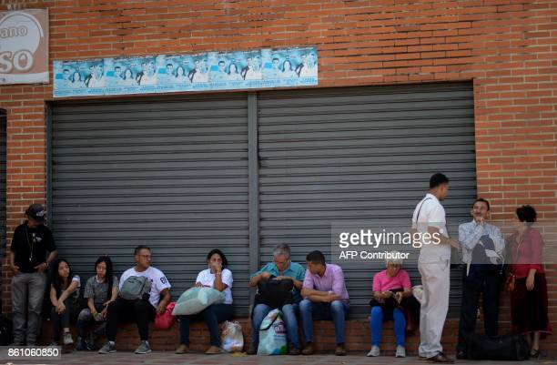 People wait to board a bus at a bus in Caracas on October 11 2017 as scores of disappointed Venezuelans who see no end to the crisis choose to leave...