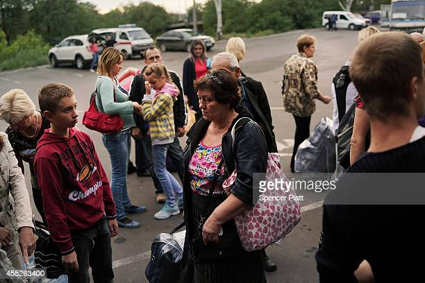 People wait to board a bus to leave the city on September 11 2014 in Donetsk Ukraine Despite a declared ceasefire between separatists forces and the...