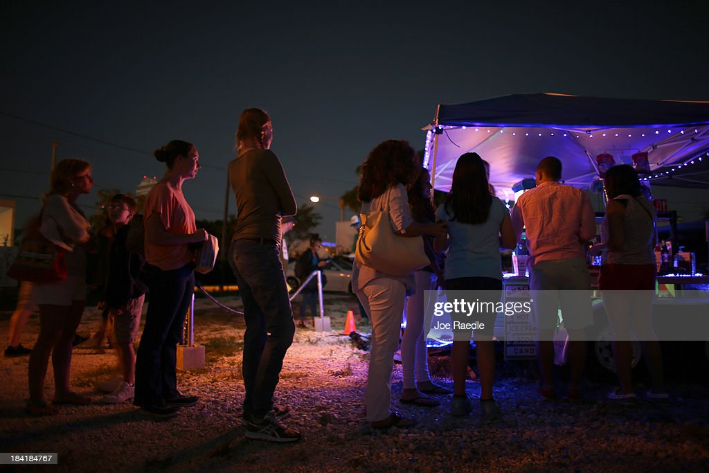 People wait to buy from the concession stand as they wait for the start of 'Back to the Future' at The Blue Starlite Mini Urban Drive-In on October 11, 2013 in Miami, Florida. Many traditional drive-in theaters around the United States have closed but the owner of The Blue Starlite held a grand opening for his small outdoor facility, which can accommodate 20 to 24 cars and has seats near the front of the viewing area, with hopes it will become popular in the urban core of Miami.