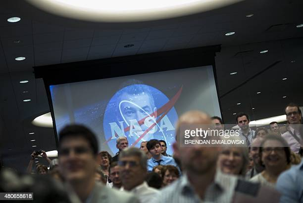 People wait to celebrate the closest flyby of Pluto by the New Horizons probe at the Johns Hopkins University Applied Physics Laboratory July 14 2015...