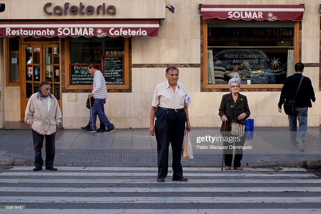 People wait to cross a road on October 11, 2012 in Madrid, Spain.Ratings agency Standard & Poor's has cut Spain's credit rating from BBB+ down to BBB-. The Spanish government has already introduced spending cuts and tax rises in an attempt to ease their debt and reduce their high unemployment levels. Spanish Economy Minister Luis de Guindos maintains that his country will not need to ask for a bailout.