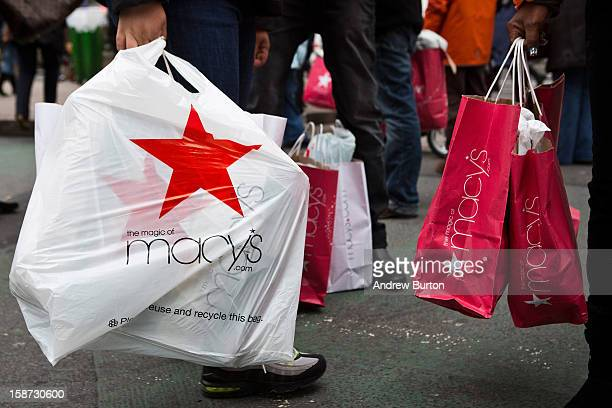 People wait to cross the street after shopping at Macy's department store on December 26 2012 in New York City Shoppers flooded Manhattan stores for...