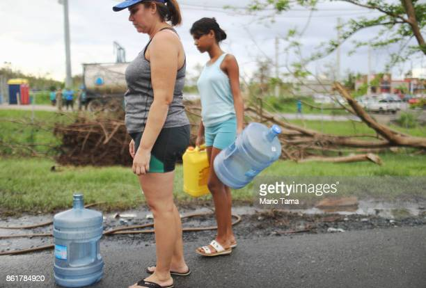 People wait to fill bottles with water provided at a pump by water authorities on October 15 2017 in Dorado Puerto Rico A CNN team found that...