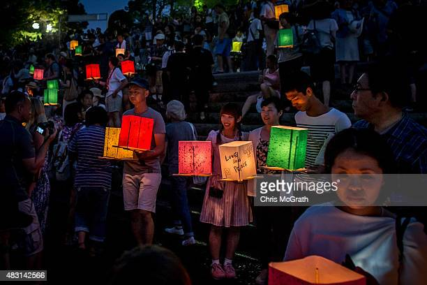 People wait to float candle lit lanterns to commemorate the 70th anniversary of the atomic bombing of Hiroshima at the Hiroshima Peace Memorial Park...