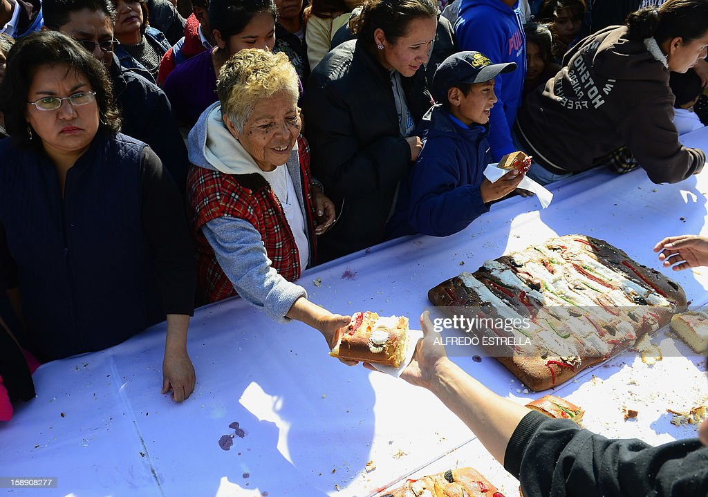 People wait to get a piece of the traditional 'Rosca de Reyes' (Mexican Epiphany Bread) --a large ring-shaped bread roll baked for Epiphany-- in Mexico City, on January 3, 2012. The 1900-metre circumference 'Rosca de Reyes', weighing 10 metric tons --the world biggest-- was distributed among 200,000 people at Zocalo Square in the Mexican capital. AFP PHOTO/Alfredo ESTRELLA