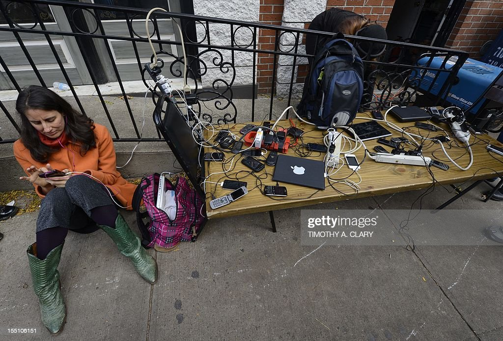 People wait to have phones and laptops charged off a generation set up in the West Village November 1, 2012 as New Yorkers cope with the aftermath of Hurricane Sandy. The storm left large parts of York City without power and transportation. The