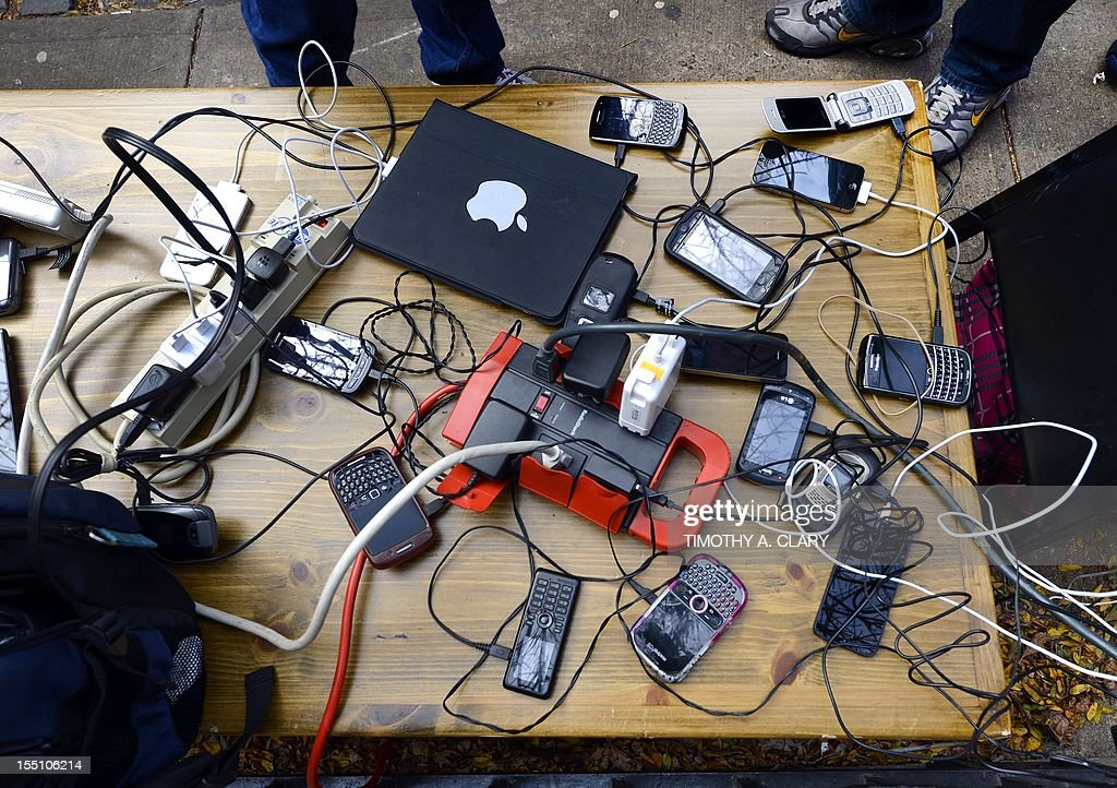 People wait to have phones and laptops charged off a generation set up in the West Village November 1, 2012 as New Yorkers cope with the aftermath of Hurricane Sandy. The storm left large parts of York City without power and transportation. The AFP PHOTO / TIMOTHY A. CLARY