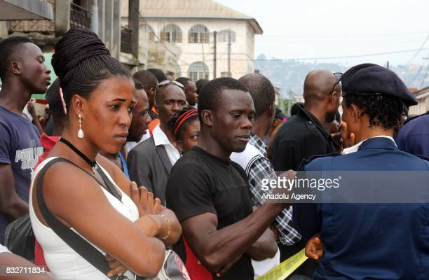 People wait to identify their relatives' bodies at Connaught hospital after landslide struck the capital of the west African state of Sierra Leone on...