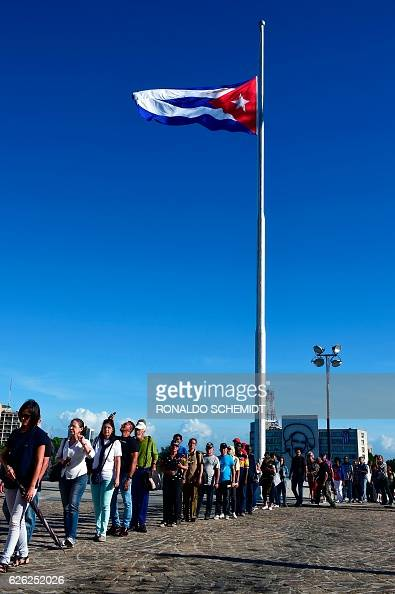 People wait to pay their last respects to Cuban revolutionary icon Fidel Castro as Cuban national flag flutters at half mast at the Revolution Square...