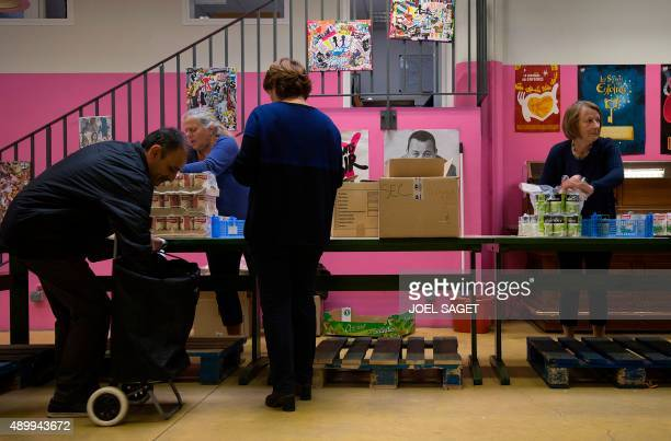 People wait to receive food during a distribution at the French charitable association 'Les Restos du Coeur' on September 24 2015 in Paris Thirty...