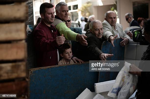 People wait to receive free merchandise distributed by Greek fruit and vegetable producers of openair markets and vendors in Athens on April 30 2014...