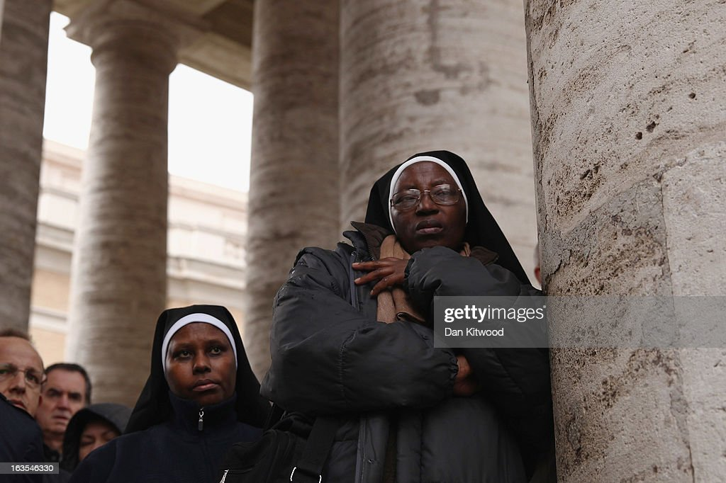 People wait under the colonnade as a rain storm passes over St Peter's Square on March 12, 2013 in Vatican City, Vatican. Pope Benedict XVI's successor is being chosen by the College of Cardinals in Conclave in the Sistine Chapel. The 115 cardinal-electors, meeting in strict secrecy, will need to reach a two-thirds-plus-one vote majority to elect the 266th Pontiff.