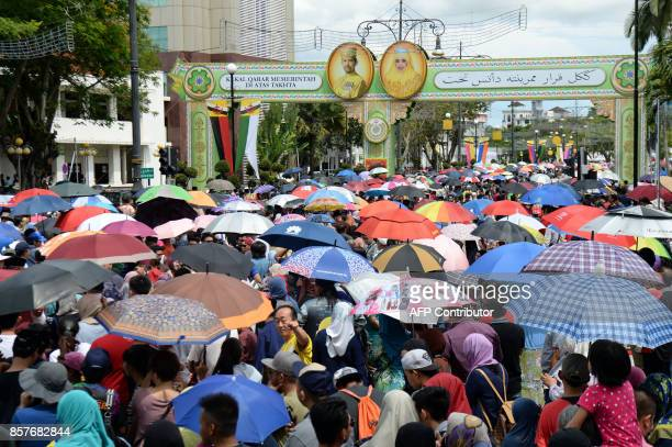 People wait under umbrellas for Brunei's Sultan Hassanal Bolkiah and Queen Saleha royal chariot to past the street during a procession to mark his...