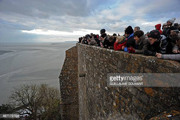 People wait watching for the wave named 'Mascaret' in front of the abbey church on the top of the MontSaintMichel on March 21 2015 Thousands of...
