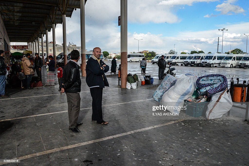 People wait with their belongings to leave kilis at a bus station on May 6, 2016 in Kilis. One person was killed and seven more wounded on May 5, 2016 when rockets fired from Syria slammed into the Turkish border region of Kilis, which has been regularly targeted by jihadists this year, the Dogan news agency said. / AFP / ILYAS