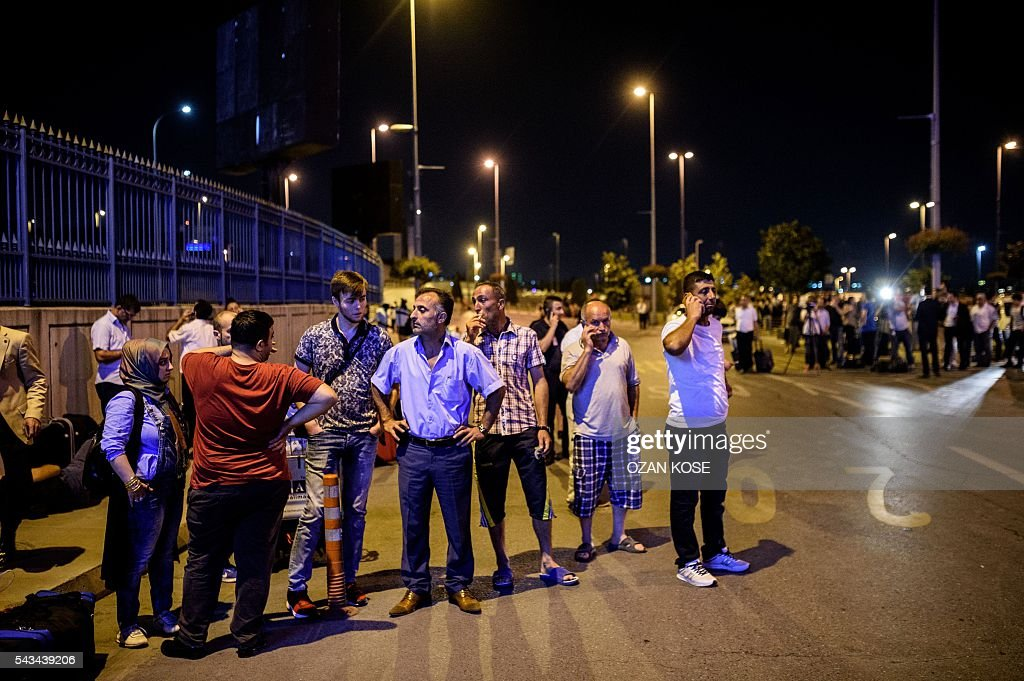 People wait with their luggage outside the Ataturk airport in Istanbul, on June 28, 2016, after two explosions followed by gunfire hit the Turkey's biggest airport, killing at least 10 people and injured 20. All flights at Istanbul's Ataturk international airport were suspended on June 28, 2016 after a suicide attack left at least 10 people dead and 20 others wounded, Turkish television stations reported. / AFP / OZAN