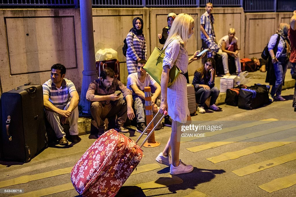 People wait with their luggage outside the Ataturk airport in Istanbul, on June 28, 2016, after two explosions followed by gunfire hit the Turkey's biggest airport, killing at least 28 people and injured 20. All flights at Istanbul's Ataturk international airport were suspended on June 28, 2016 after a suicide attack left at least 10 people dead and 20 others wounded, Turkish television stations reported. / AFP / OZAN