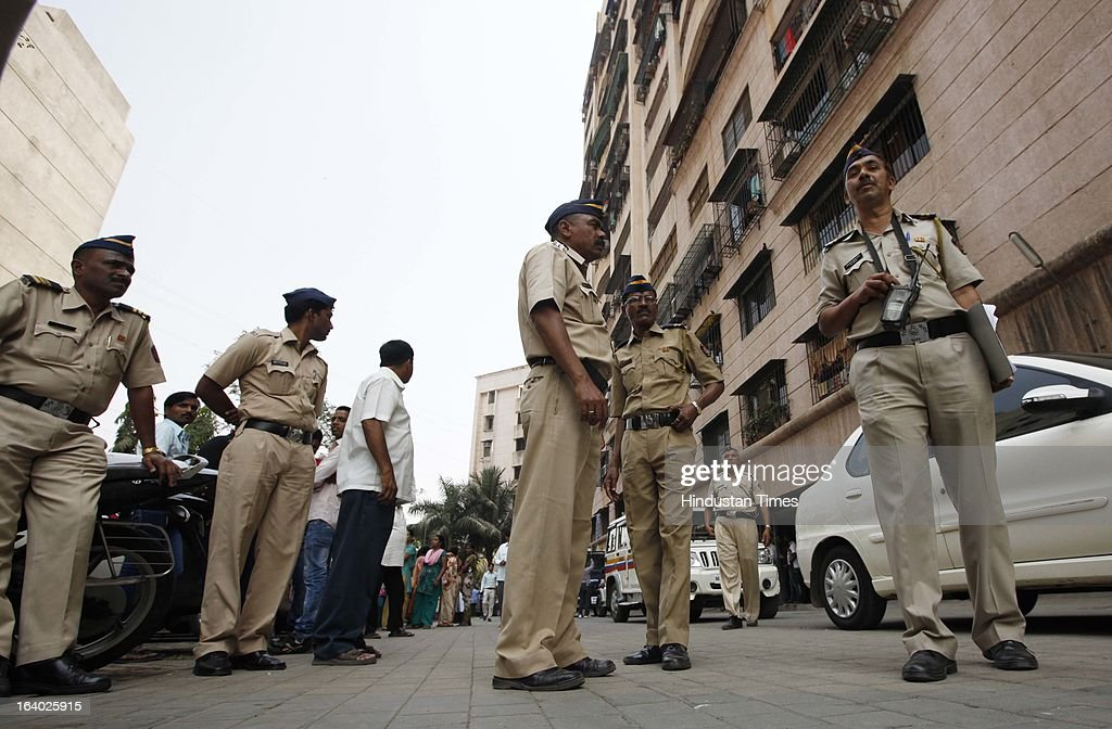 People waiting at the main gate of Odyssey building in Bhakti Park, Wadala on March 18, 2013 in Mumbai, India. A couple and their two young children were found dead in their one-bedroom apartment. All the bodies had black polythene bags pulled over their faces. From the extent of decomposition, it appeared that they had been dead for at least a day and a half, police said.