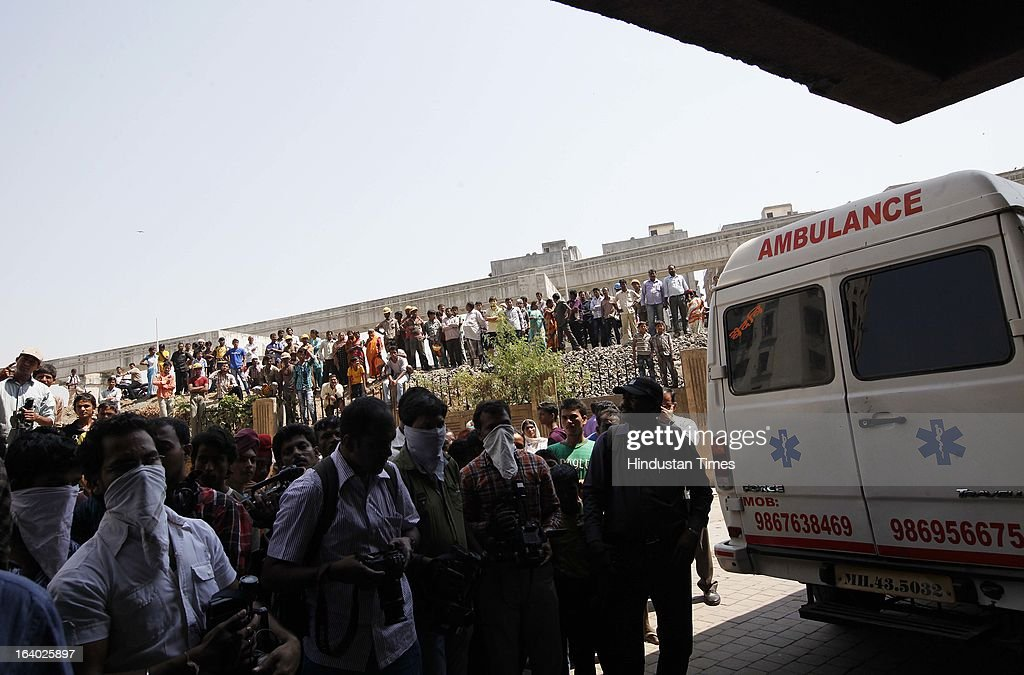 People waiting at the rear gate of Odyssey building in Bhakti Park, Wadala on March 18, 2013 in Mumbai, India. A couple and their two young children were found dead in their one-bedroom apartment. All the bodies had black polythene bags pulled over their faces. From the extent of decomposition, it appeared that they had been dead for at least a day and a half, police said.