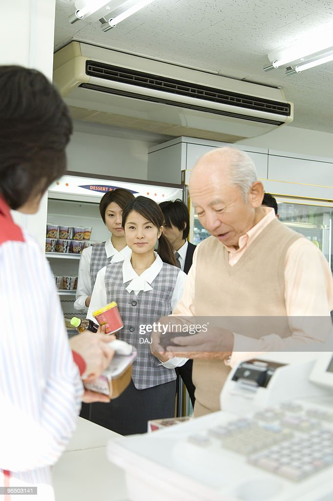 People waiting in line at cash register : Stock Photo
