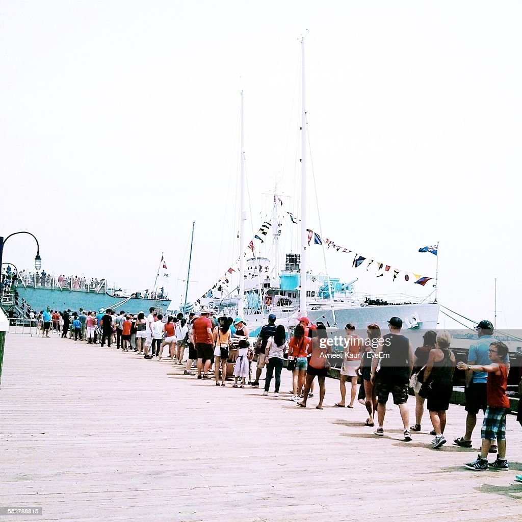 People Waiting In Line For Ferry Against Clear Sky