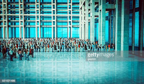 Personas esperando en línea, edificio de oficinas