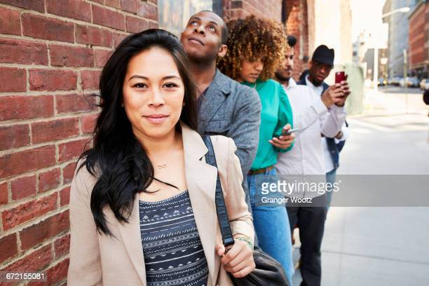 People waiting in line on sidewalk with cell phones