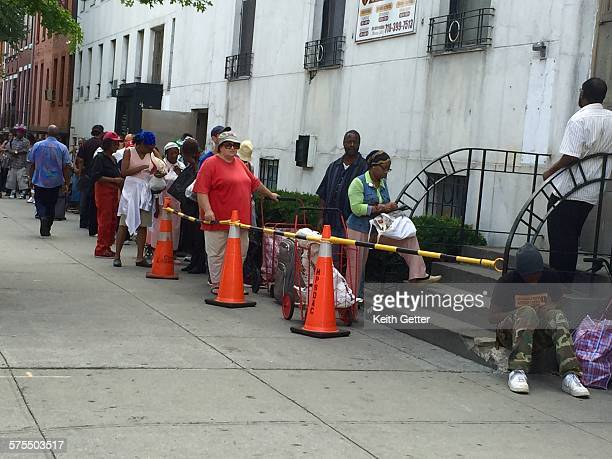 People waiting on a line on the sidewalk to get free food from a community food pantry in Brooklyn NYC August 202015