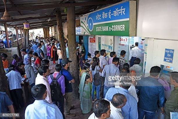 People waiting outside in a queue to exchange their old currency notes with the new one and deposit cheque at SBI Bank Thane on November 21 2016 in...