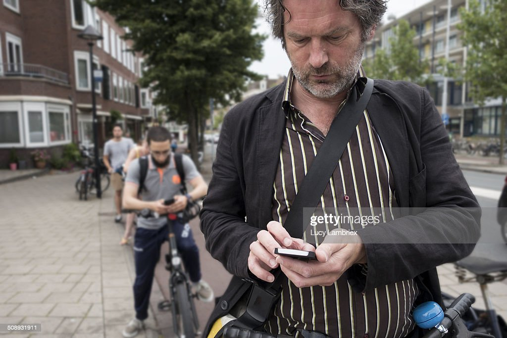 People waiting with bikes, using smart phones