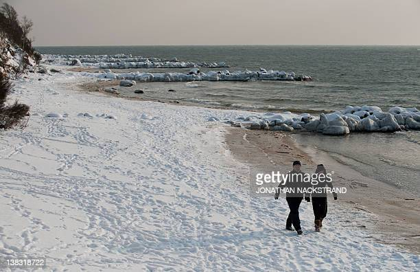 People waks on February 5 2012 on the shore near the city of Ronne on the Danish island of Bornholm in the Baltic Sea The deadly cold snap that has...