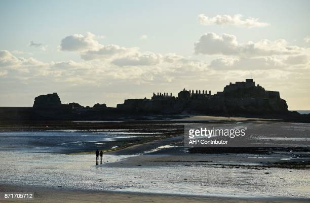 People walk accross the sand at low tide towards the Elizabeth Castle in St Aubins's Bay from St Helier on the British island of Jersey on November 8...