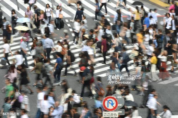 People walk across a zebra crossing at an intersection in Tokyo on September 15 2017 Millions of Japanese woke up in the early hours on September 15...