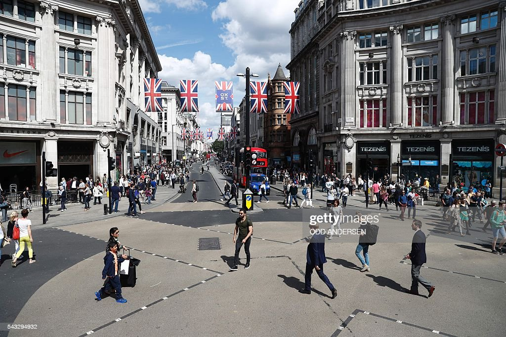 People walk across oxford Circus as Union flags hang across Oxford Street in central london on June 27, 2016. Shares in banks, airlines and property companies plunged on the London stock exchange Monday as investors singled out the three sectors as being the most vulnerable to Britain's decision to leave the EU. / AFP / ODD