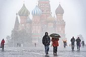 People walk across Red Square during a snowfall in Moscow on October 9 2015 AFP PHOTO / DMITRY SEREBRYAKOV