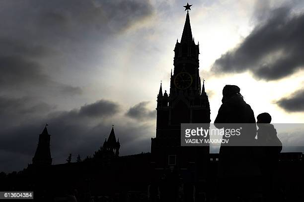 People walk across Red Square with the Kremlin's Spasskaya Tower seen in the background in central Moscow on October 9 2016 MAXIMOV