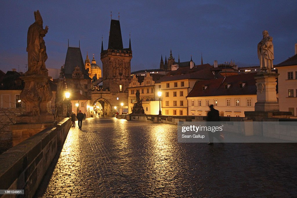 People walk across the Charles Bridge on the side closer to Mala Strana early in the morning on December 21 2011 in Prague Czech Republic Prague is...