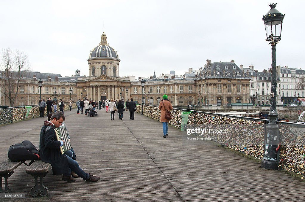 People walk across the Pont des Arts on January 4, 2013 in Paris, France. The nine-arch metallic footbridge completed in 1804 is one of the most romantic places of the capital where people visit it to attach love padlocks illustrated with their initials or messages of love, before throwing the key into the River Seine. The bridge is also a meeting place for artists who find inspiration from the surrounding views of the city.
