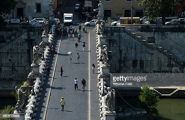 People walk across the Ponte Sant'Angelo bridge as seen from the Castel Sant'Angelo in Rome on July 16 2015 AFP PHOTO / TIZIANA FABI