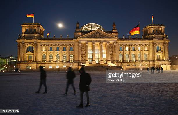 People walk across the snowcovered lawn in front of the Reichstag on January 22 2016 in Berlin Germany The Reichstag is the seat of the Bundestag...