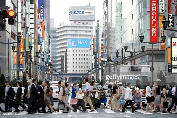 People walk across the street in the Ginza district on July 10 2009 in Tokyo Japan Tokyo has become the most expensive city for expatriates in the...