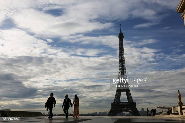 People walk across the Trocadeo Plaza at sunrise in front of the Eiffel Tower on May 12 2017 in Paris / AFP PHOTO / LUDOVIC MARIN