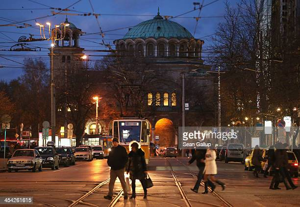 People walk across the Vitosha Boulevard shopping street as the St Nedelya Eastern Orthodox church stands behind at twilight on December 7 2013 in...