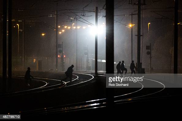 People walk across train tracks near the Eurotunnel terminal in Coquelles on August 3 2015 in Calais France Hundreds of migrants are continuing to...