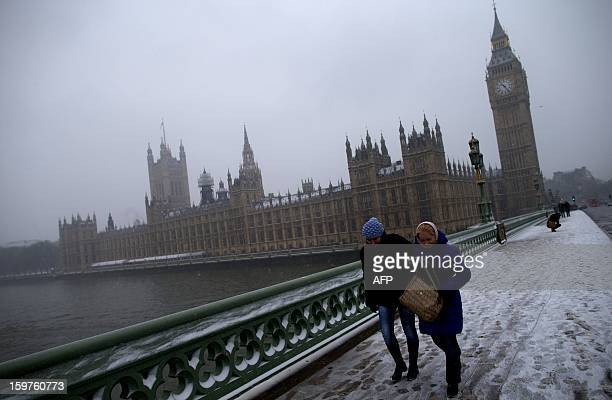 People walk across Westminster Bridge during snowfall in central London on January 20 2013 Passengers were forced to sleep on the floor at London's...