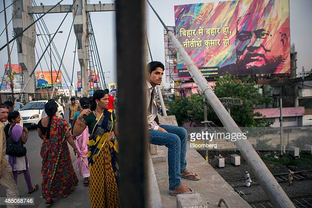 People walk along a bridge past election billboard advertisements in Patna Bihar India on Monday July 27 2015 More than anywhere Bihar reflects the...