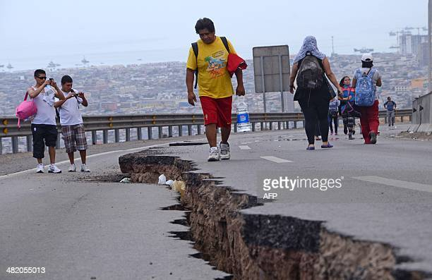 People walk along a cracked road in Iquique northern Chile on April 2 2014 a day after a powerful 82magnitude earthquake hit off Chile's Pacific...
