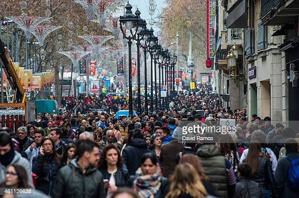People walk along a crowed shopping street on the first day of the winter sales on January 7 2015 in Barcelona Spain The Spanish labor market has...