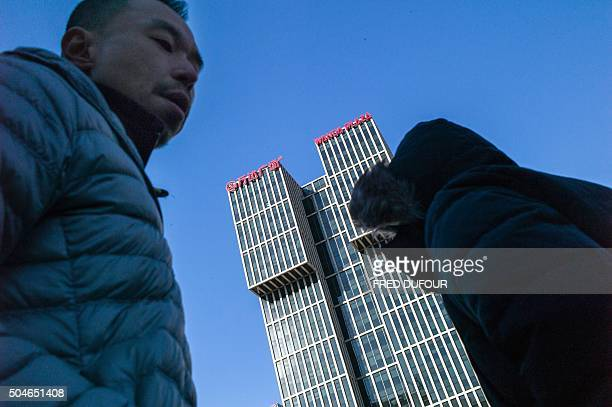 TOPSHOT People walk along a road before the Chinese conglomerate Wanda Group building in Beijing on January 12 2016 Chinese conglomerate Wanda Group...